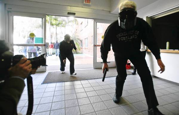 San Diego State chaplain Dana Garrett, left, and retired police officer Chuck Harold enter a university residence hall as they simulate a police team searching for a gunman during a training exercise.