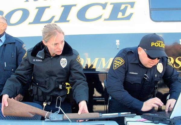 Tucson police officers catalog firearms during a gun buyback program on the second anniversary of the shooting in the city that killed six people and injured 13, including then-Rep. Gabrielle Giffords.