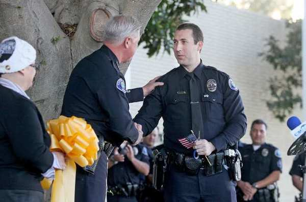 "Officer Jon Smith, right, shakes hands with Police Chief Tom Gazsi during a ""yellow ribbon-cutting"" ceremony in from of Costa Mesa Police Department by City Hall on Tuesday. In November 2011, Smith was deployed with the 425th Civil Affairs Battalion, to serve in Afghanistans Operation Enduring Freedom."