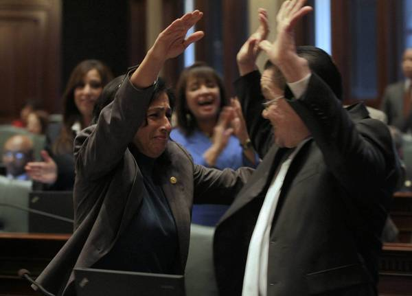 Rep. Edward Acevedo is congratulated by Rep. Lisa Hernandez on the passage of his bill to provide driver's licenses to illegal immigrants.