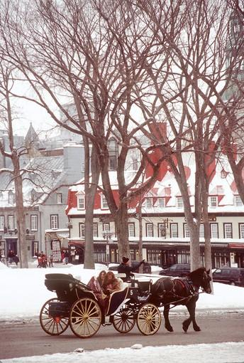 Passengers in a horse-drawn buggy bundle up for a ride thorugh the streets of old Quebec City during winter Carnaval