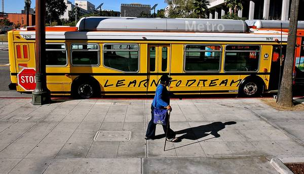 "A pedestrian passes a Metro bus that has been painted to look like a school bus as part of the ""Arts Matter"" campaign."