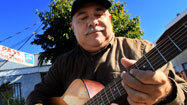 Hector Gonzalez straps a five-string bass guitar over his belly inside a music studio on a dreary stretch of Monterey Park. He plays as a smooth, prerecorded tenor joins a funky accordion through his headphones.