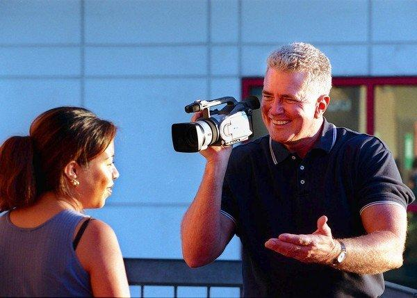 Huell Howser with his camera interviews Marleni Salgado.