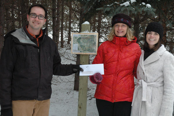 Charles Dawley (from left), stewardship and geographic information systems specialist for the Little Traverse Conservancy, receives a check from Maureen Radke with the Charlevoix County Community Foundation and Sara Ward with the Petoskey-Harbor Springs Area Community Foundation at the Wisser-Saworski Nature Preserve near Boyne Falls. The donation helped fund the Web hosting of a conservancy smartphone app.