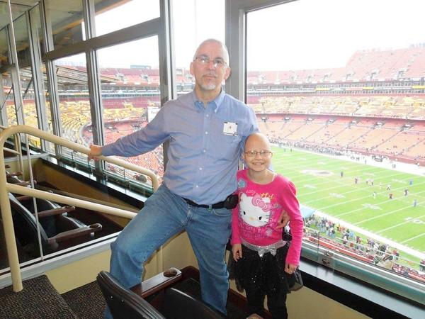 Manchester residents John Carver and his daughter, Juliana, pose in the suite at FedEx Field in Landover where they watched the Redskins defeat the Ravens, 31-28, in overtime on Dec. 9.