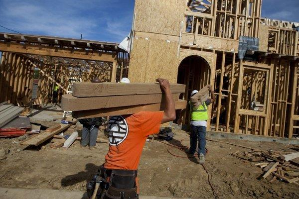 Workers carry stacks of lumber into a house under construction at a development in Rancho Santa Fe, California.