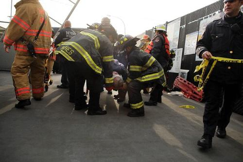 An injured person is carried to a waiting ambulance following an early morning ferry accident during rush hour in Lower Manhattan on January 9, 2013 in New York City.