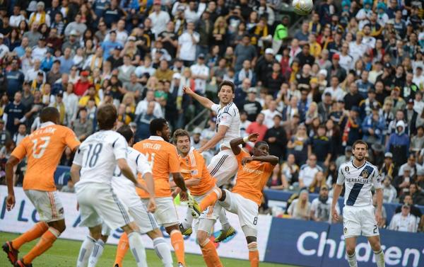 The Galaxy's Omar Gonzalez, top, scores on a header during the MLS Cup game between the Galaxy and Houston Dynamo on Dec. 1.