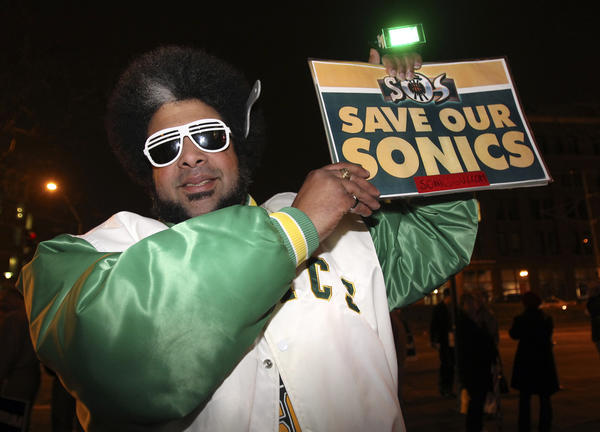 Kris Brannon, a fan of the Supersonics, holds up a 'Save our Sonics' sign during a campaign rally for Republican presidential candidate Rick Santorum in Tacoma in February 2012.
