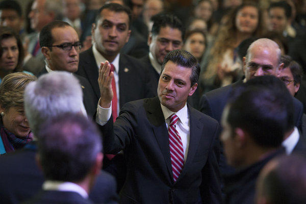 Mexican President Enrique Pena Nieto, center, arrives Wednesday at a gathering in Mexico City. The government enacted legislation during the day requiring authorities to assist victims of violence and establish a fund for possible reparations.