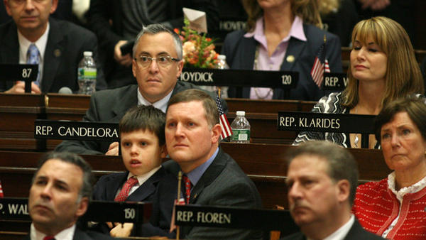 State House members including Rep. Stephen G. Walko and his son listen as Gov. Dannel P. Malloy speaks of Newtown during Malloy's speech Wednesday to the General Assembly.
