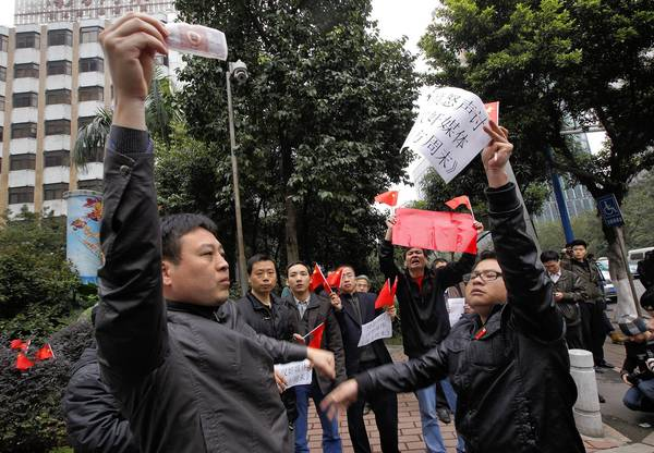A supporter of the Southern Weekly, left, confronts an ideological rival outside the paper's headquarters in Guangzhou, China.