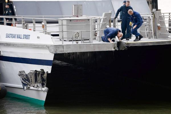 Investigators look over the damage to the front of a commuter ferry from New Jersey after it struck a Manhattan dock.