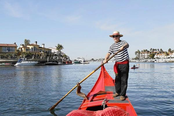 """Tim """"Bepi"""" Reinard, owner of Sunset Gondola, shares stories as he gives members of the media a tour of Huntington Beach Harbor."""
