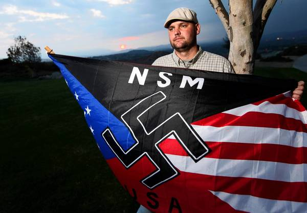 Jeffrey Hall holds a neo-Nazi flag in Riverside in 2010. He was fatally shot by his son in May 2011.