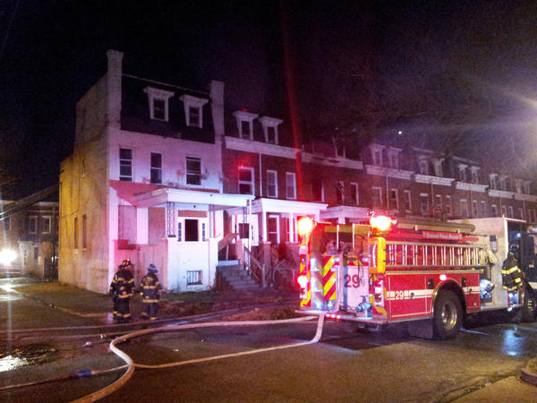 Firefighters attend to a two-alarm fire in West Baltimore that burned three houses.