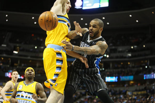 Orlando Magic guard Jameer Nelson (14) passes the ball around Denver Nuggets center Kosta Koufos (left) during the first half at the Pepsi Center.