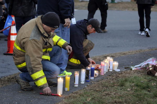Firefighters move memorial candles away from bouquets and stuffed animals that were left at a makeshift memorial near Sandy Hook Elementary School Saturday.