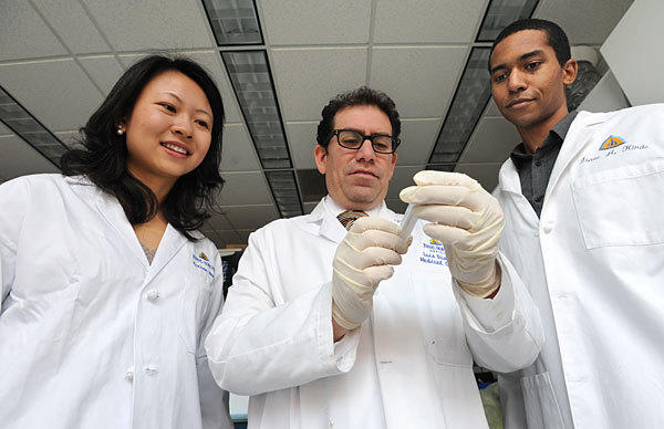 Dr. Luis Diaz holds a vial of a pap smear. He is senior researcher on whether the tests can be used to detect ovarian and endometrial cancer. Graduate students Isaac Kinde and Yuzuan Wang are authors of the research