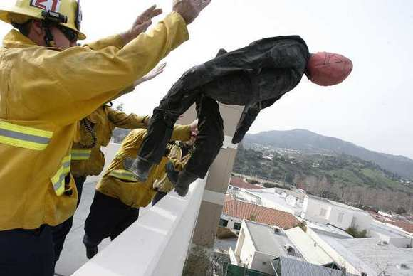 Pasadena firefighters throw a dummy over a pedestrian bridge to demonstrate the rescue inflatable used to attempt to catch people who fall from high places to the Glendale Police Department at Glendale Community College on Wednesday, January 8, 2013.