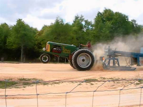 Rob Waller pops a wheelie with his 1948 green Oliver tractor as he pulls a sled.