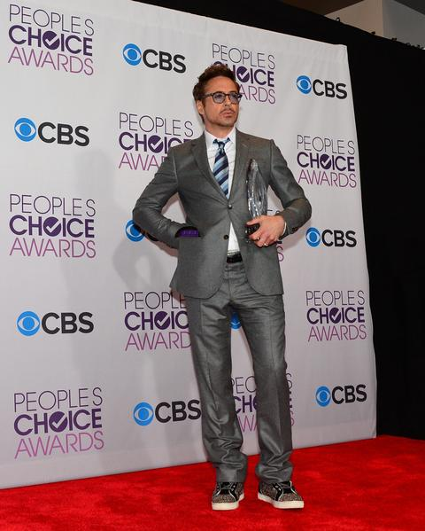 Robert Downey, Jr. in a gray suit and sneakers.