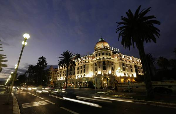Cars drive along the Promenade des Anglais near the Negresco Hotel at sunset in Nice, southeastern France, January 8, 2013. The five-star Negresco, which marks its 100th anniversary, has been host to politician Winston Churchill, twenty-five African heads of state, along with Hollywood star Gary Cooper and singers Michael Jackson and Elton John.