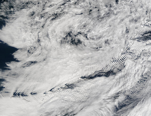Clouds cover this true-color Terra MODIS image of the Bering Sea (top), Alaska's Aleutian Islands, and the northern Pacific Ocean (bottom). As the clouds passed over the Islands, the islands forced the air to moved around them, and consequently caused wakes to form in the clouds, much like those that would form from a ship¿s passage through water. This image was acquired September 6, 2002.
