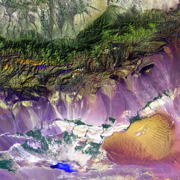 The Turpan Depression, nestled at the foot of China's Bogda Mountains, is a strange mix of salt lakes and sand dunes. It is one of the few landscapes in the world that lies below sea level.  This image was acquired by Landsat 7's Enhanced Thematic Mapper plus (ETM+) sensor.
