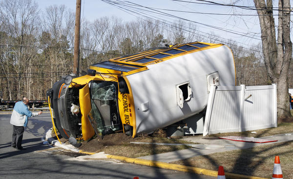 An investigator examines an overturned school bus resting on a fence after colliding with a commuter bus in Old Bridge, N.J. The New York City-bound commuter bus and the school minibus crashed on a state highway, injuring at least 19 people, two critically. School officials said no students were on the school bus, which landed on its side along Route 9.
