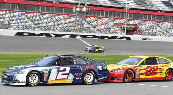 Brad Keselowski (2) and Joey Logano (22) are nose-to-tail as they wait on pit road while Jeff Gordon (24) crosses the start/finish line during testing during NASCAR Sprint Cup Series Preseason Thunder at Daytona International Speedway in Daytona Beach, FL, on Thursday, January 10, 2013.