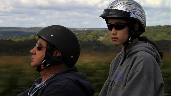"Ann Boccutti rides a motorcycle with her father Bob Boccutti in ""Somewhere Between."""