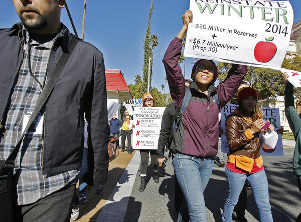 PCC students, carrying picket signs walk across Colorado Blvd. with several Pasadena City College students and faculty in a protest at Pasadena City College on Thursday, January 10, 2013. Students and faculty are upset about the handling of the school's budgets and the cuts that are effecting them.