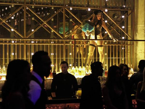 A burlesque dancer stands over the bar at the Emerson Theatre, a space designed to resemble a Prohibition-era burlesque club.