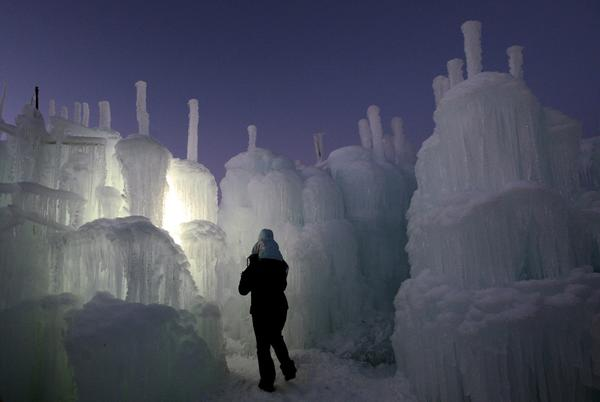 A man and child walk through the Ice Castles on New Year's Eve, the day of their public debut.