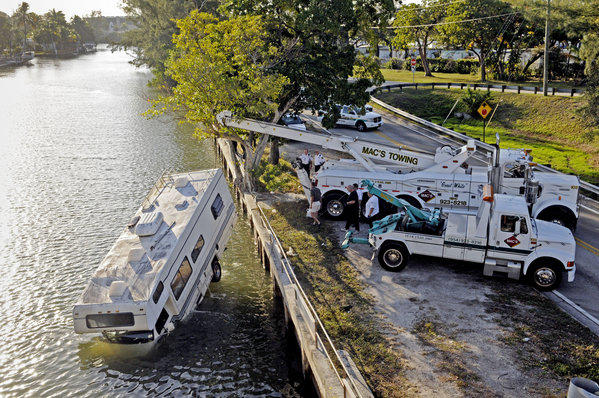 .Mac's Towing pulls a Coachmen RV out from a canal alongside Old Griffin Road in Dania Beach.