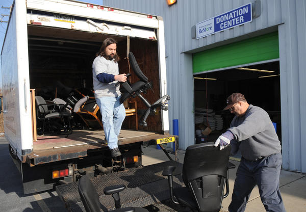 (from left) Volunteers Christian Herr of Topton and Jim Yanora of Allentown take donated office chairs off a truck and into the donation center. Habitat for Humanity Lehigh Valley will open the retail store, Habitat Lehigh Valley ReStore at 1053 Grape Street in Whitehall inside part of the former Circuit City. The store will offer customers used/new items for their homes at bargain prices and benefit Habitat for Humanity.