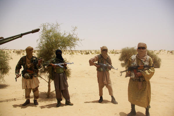 Fighters from Islamist group Ansar Dine stand guard during a hostage release in the desert outside Timbuktu, Mali, on April 24, 2012.