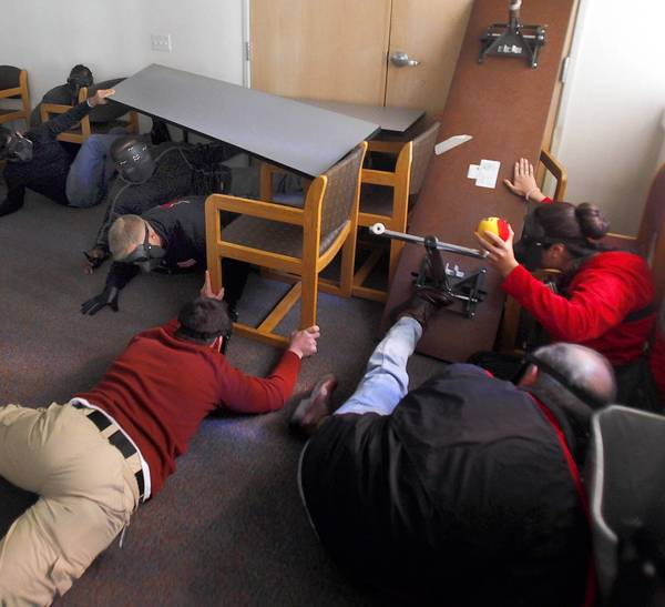 Participants acting as students and teachers at San Diego State attempt to barricade themselves in a room in the Olmeca Residence Hall while a simulated active mass shooting suspect was trying to crash through.
