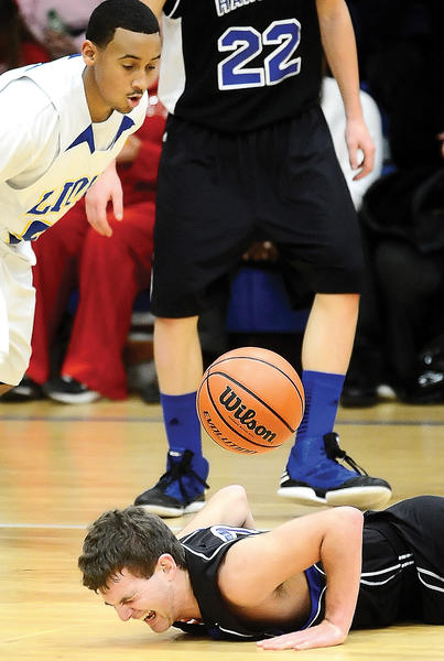 Hancock's Jordan Tosten grimaces in pain after falling during the first half of Thursday night's boys basketball game at Broadfording.
