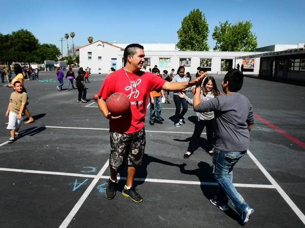 Coach Luciano Mondolo, center, plays four square with students at Cesar Chavez Elementary School in Norwalk. Gov. Jerry Brown's budget plan would shift some funds from wealthy suburban districts to campuses that serve poor students and non-English speakers.