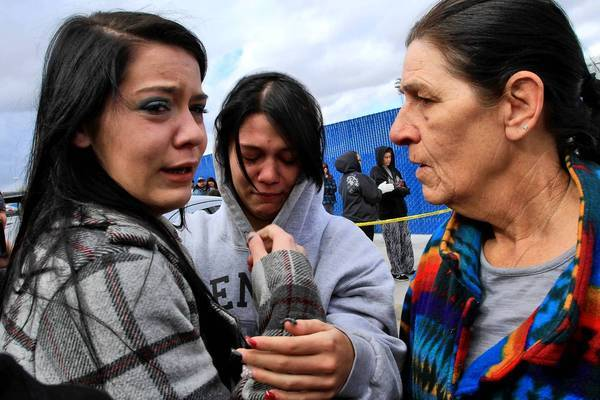 Tyler Smith, 18, left, weeps after reuniting with her 15-year-old sister Paige, who was stuck inside Taft High School after the shooting.