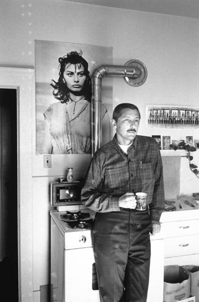 In this undated photo, author Evan S. Connell Jr. holds a mug of coffee as he stands next to the stove in his kitchen, which is embellished with a large movie poster of Sophia Loren. Connell, a literary iconoclast whose writings as a novelist, poet, essayist and historian won the admiration of critics and a cult-like following of discerning readers, has died in Santa Fe, N.M. He was 88.