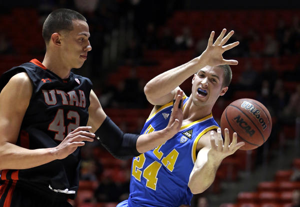 Utah center Jason Washburn knocks the ball from UCLA forward Travis Wear in the first half Thursday night.