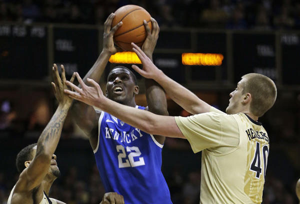 Kentucky forward Alex Poythress (22) drives between Vanderbilt defenders Kedren Johnson, left, and Josh Henderson (40) in the first half of an NCAA college basketball game on Thursday, Jan. 10, 2013, in Nashville, Tenn.