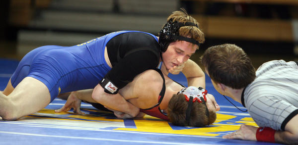 Aberdeen Central's Griffin Hieb works to pin Brooking's Ty Johnson as referee Jason Hill, right, looks on during their 138-pound bout Thursday night at the Golden Eagles Arena.