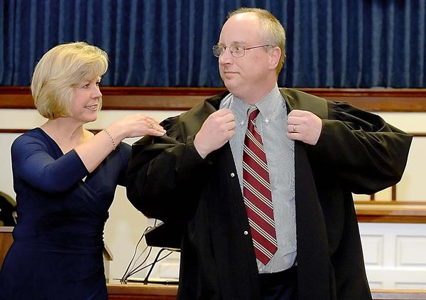 Maria Lorensen helps her husband, Michael D. Lorensen, put on his judicial robe after he was sworn in Thursday as the newest judge in West Virginia's 23rd Judicial Circuit. The ceremony was held at the Berkeley County Courthouse in Martinsburg, W.Va.