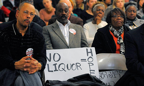 Preston Greene (left), president of Howard Park Civic Association, sits beside his sign during a Planning Commission meeting on the proposed zoning code legislation.