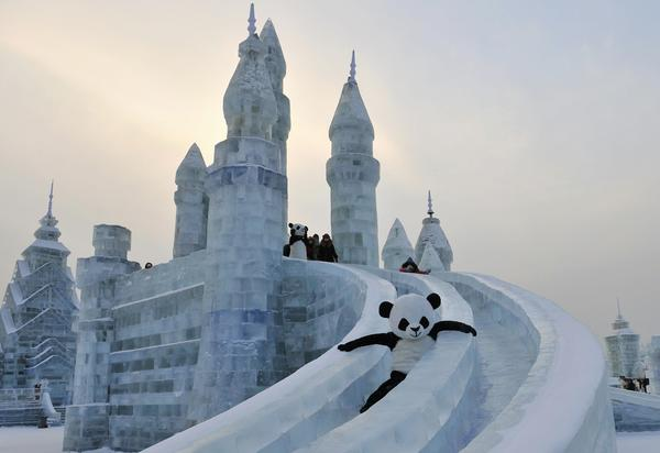 An employee wearing a panda costume slides down from an ice sculpture during the Harbin International Ice and Snow World festival in Harbin, China.
